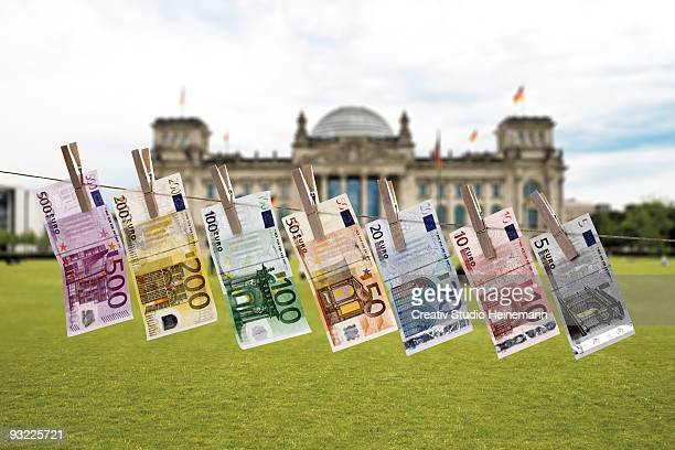 germany, berlin, euro bank notes hanging on clothesline, reichstag building in background - five euro banknote stock photos and pictures