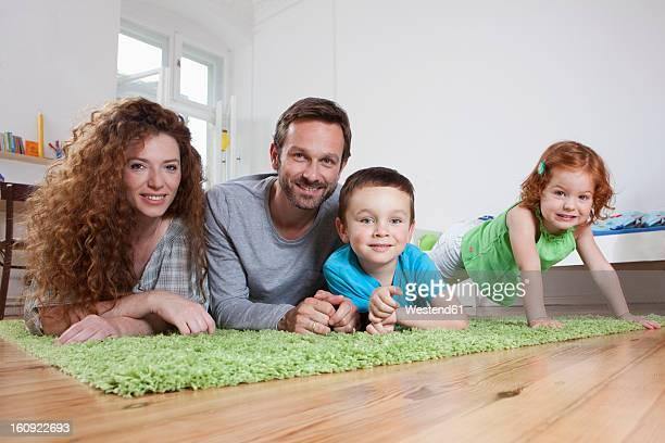 Germany, Berlin, Family relaxing on floor, smiling, portrait
