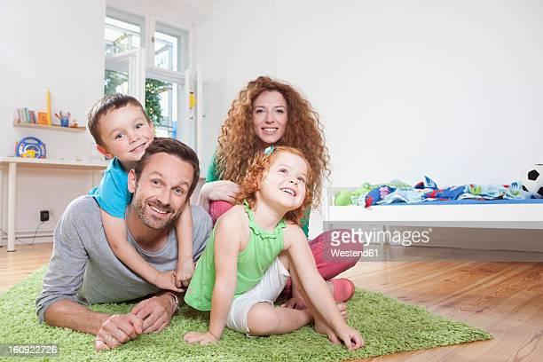 Germany, Berlin, Family sitting on floor, smiling, portrait