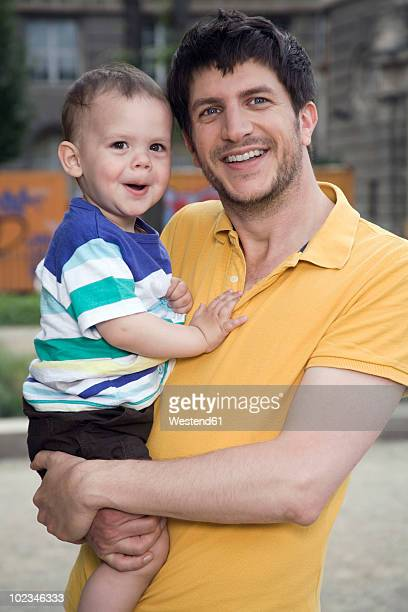 Germany, Berlin, Father carrying son (18-23 months) looking away, smiling