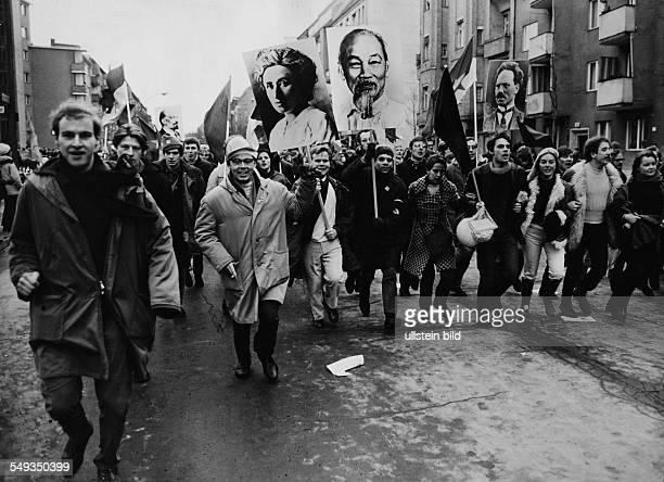 Germany Berlin February 1968 VietnamDemonstration young people carrying flags and poster with photographs of Ho Chi Minh and Rosa Luxemburg