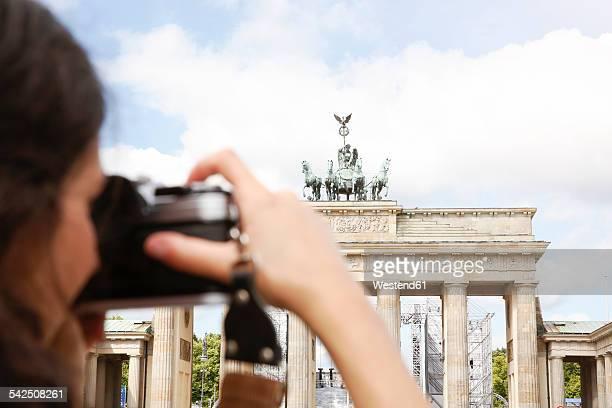 Germany, Berlin, female tourist photographing Brandenburg Gate