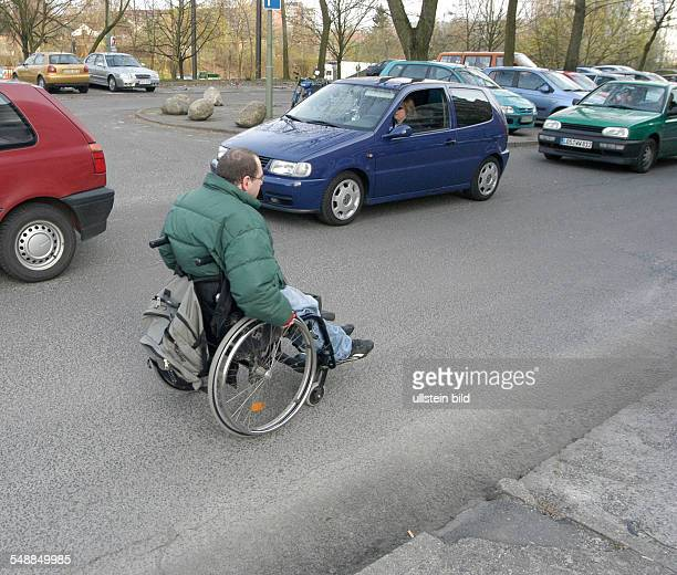 Germany Berlin - handicapped man in wheel chair is using the driving surface because of the high road kerb he cannot reach the pavement -