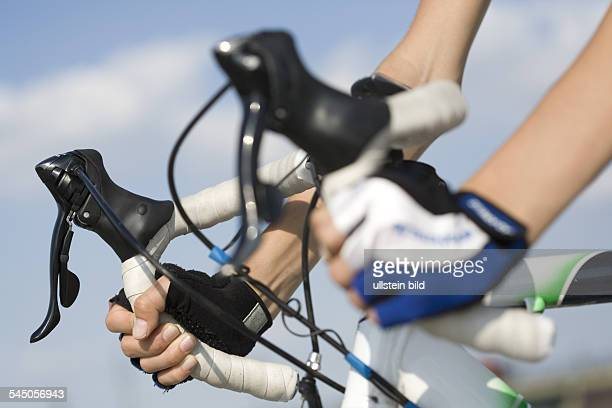 Hands of a racing cyclist holding the drop handle bar
