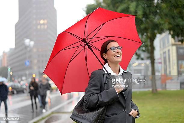 Germany, Berlin, happy businesswoman with red umbrella at Potsdamer Platz