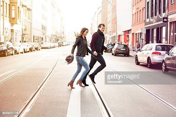 germany, berlin, happy couple crossing a street - holding hands in car stockfoto's en -beelden