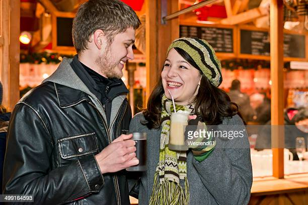 Germany, Berlin, happy young couple with hot beverages at Christmas market