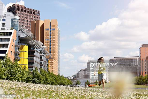 Germany, Berlin, happy young woman running on a meadow near Potsdam Square