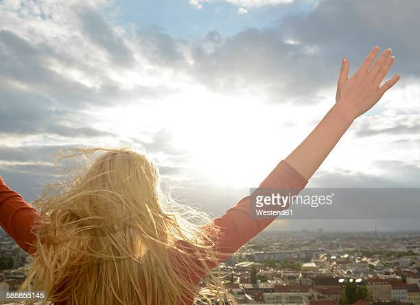Germany, Berlin, happy young woman with arms up looking at view