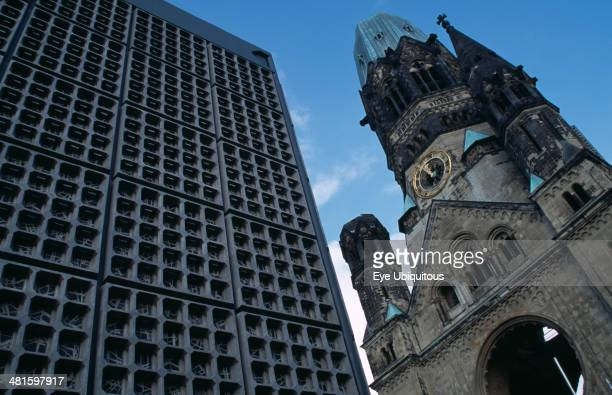 Germany Berlin Kaiser Wilhelm Memorial Church Part view of ruined gothic exterior with clock face beside new building
