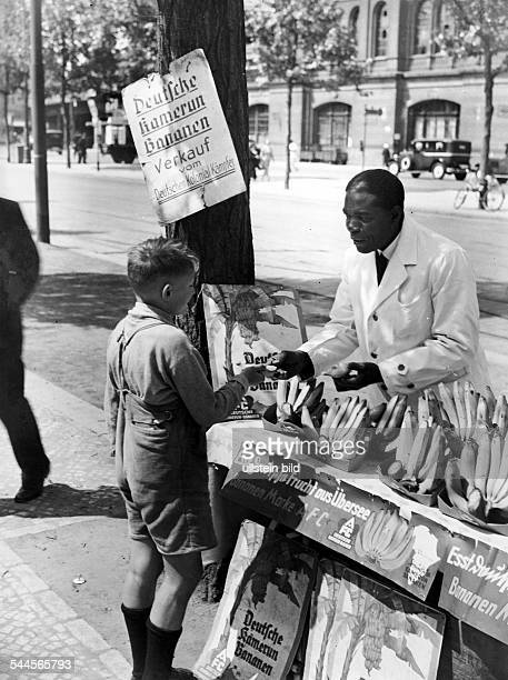 """Germany Berlin - man, former soldier of the German protection forces at Kamerun, selling """"German Kamerun Bananen"""" from a sales stall - um 1929"""