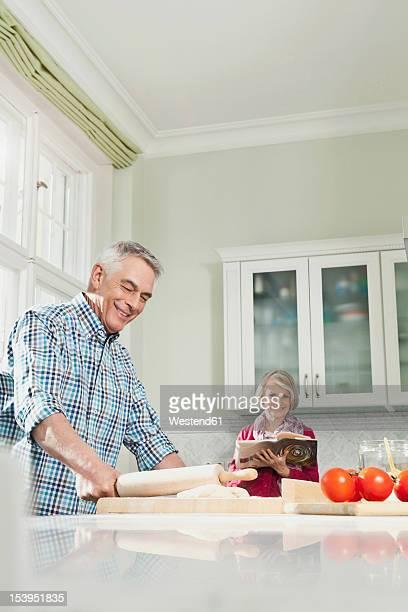Germany, Berlin, Man preparing food, woman with book in background