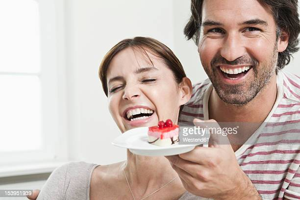 Germany, Berlin, Man surprising woman with serving cake
