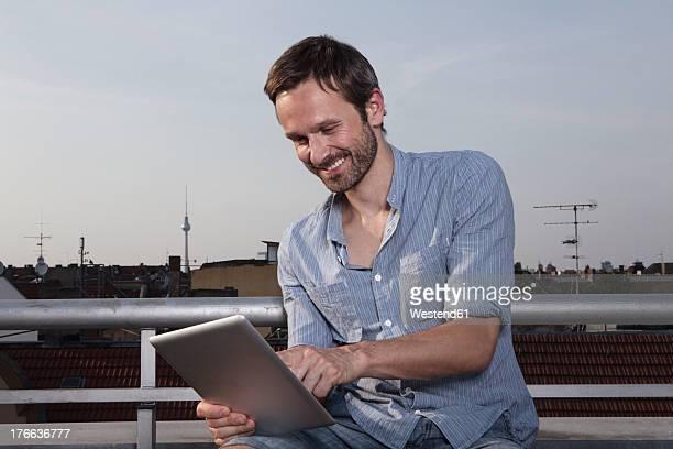 Germany, Berlin, Man using digital tablet on roof terrace, smiling