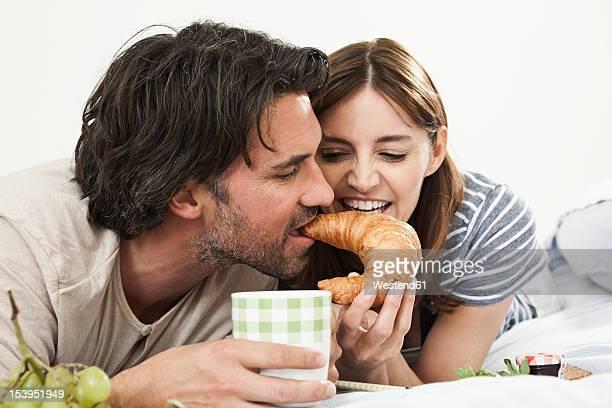 Germany, Berlin, Mature couple having breakfast in bed