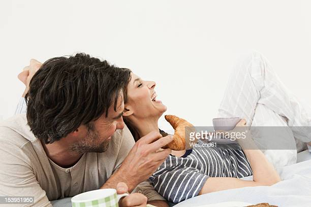 germany, berlin, mature couple having breakfast in bed - breakfast in bed stock pictures, royalty-free photos & images