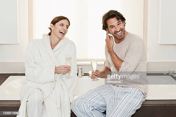 germany, berlin, mature couple sitting on bathtub with sparkling wine - couple bathtub stock pictures, royalty-free photos & images