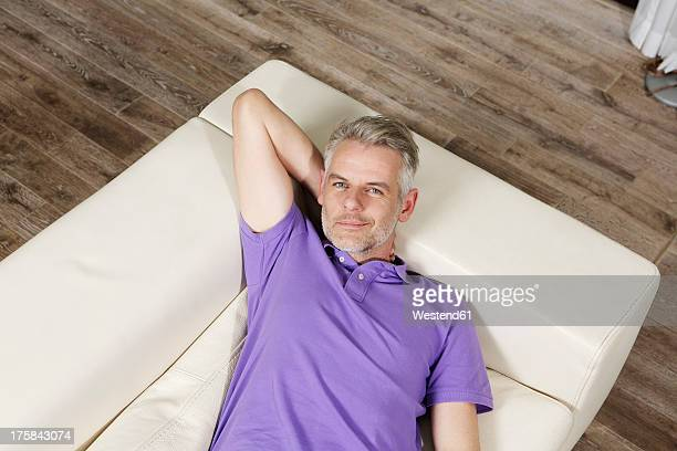 Germany, Berlin, Mature man lying on sofa, smiling, portrait