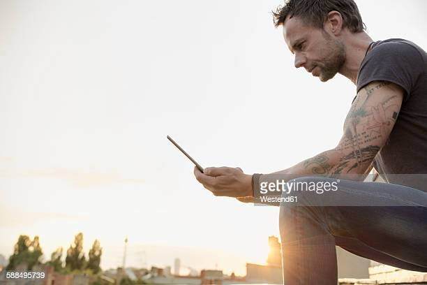 Germany, Berlin, Mature man on roof terrace using digital tablet