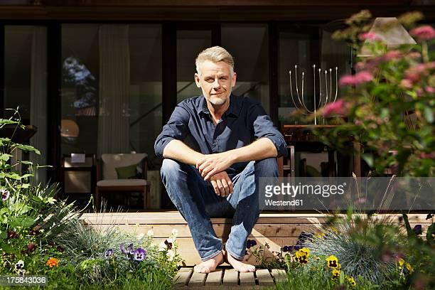 Germany, Berlin, Mature man relaxing on terrace, smiling, portrait