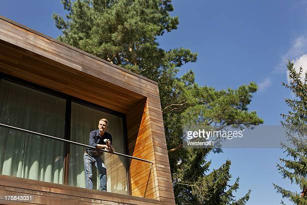 Germany, Berlin, Mature man standing on balcony and relaxing