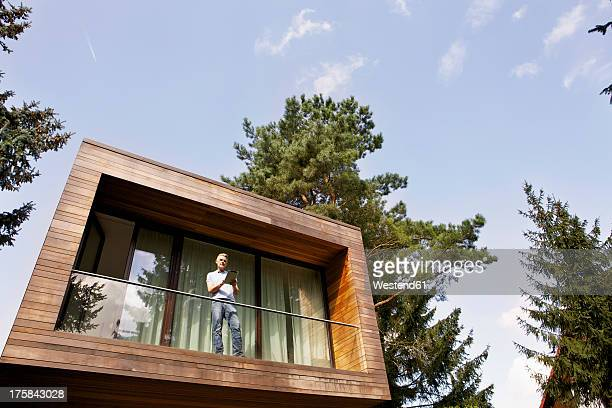 Germany, Berlin, Mature man standing on balcony and using tablet