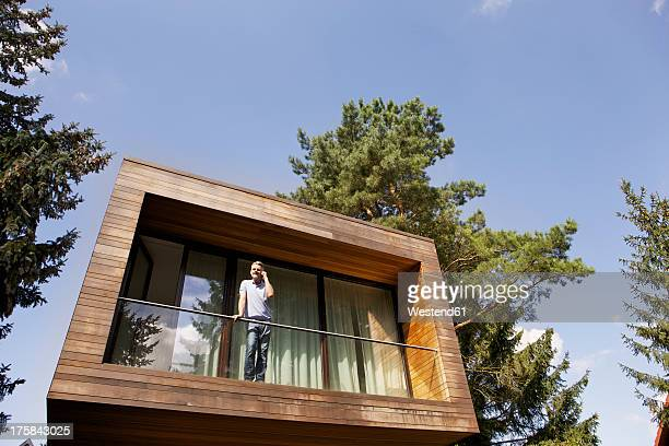 Germany, Berlin, Mature man standing on balcony with mobile phone