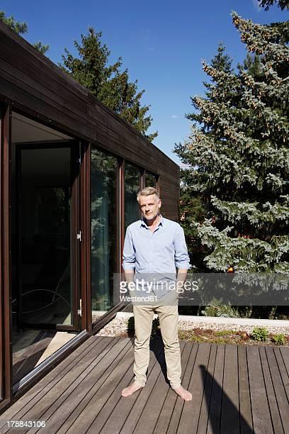 germany, berlin, mature man standing on terrace, portrait - einzelner mann über 40 stock-fotos und bilder