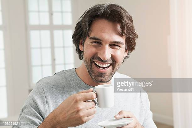 Germany, Berlin, Mature man with coffee cup, smiling, portrait