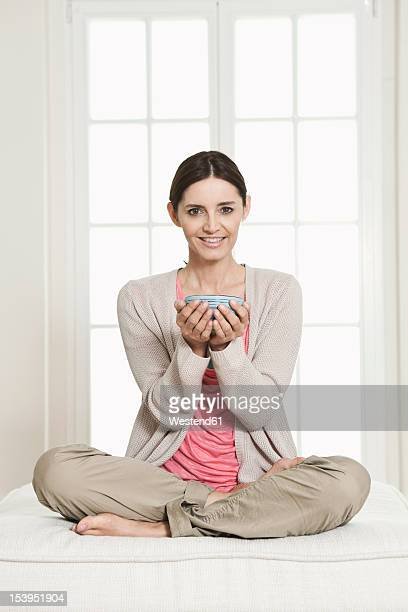 Germany, Berlin, Mature woman holding bowl, smiling, portrait