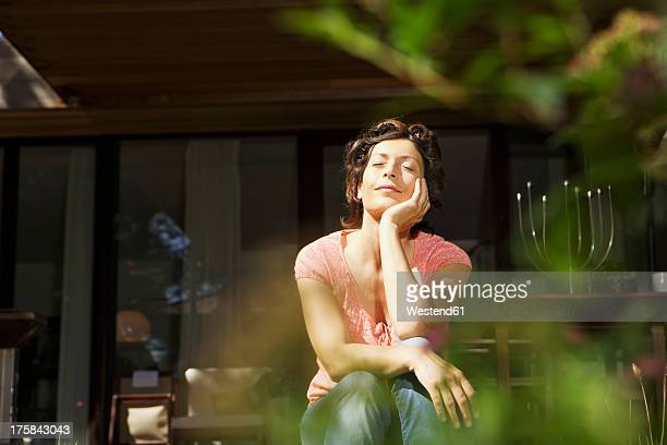 Germany, Berlin, Mature woman relaxing on terrace