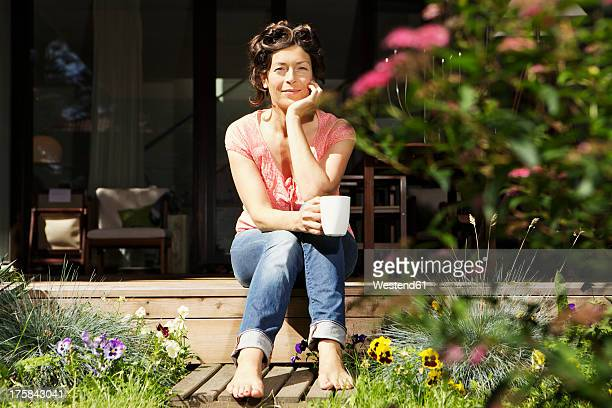 Germany, Berlin, Mature woman relaxing on terrace, smiling, portrait