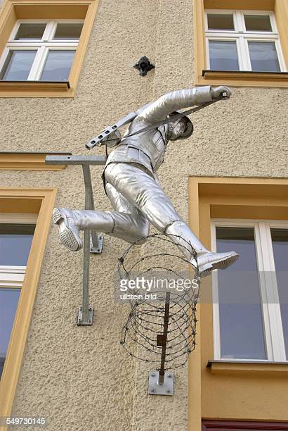 Germany Berlin memorial sites / monuments to the former 'Berlin wall' Sculpture of former GDR border police man Conrad Schumann jumping over the...