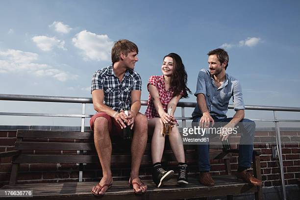 Germany, Berlin, Men and woman sitting on roof terrace, smiling