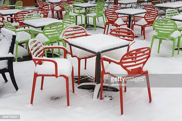 chairs and tables covered with snow in front of a cafe at square Alexanderplatz