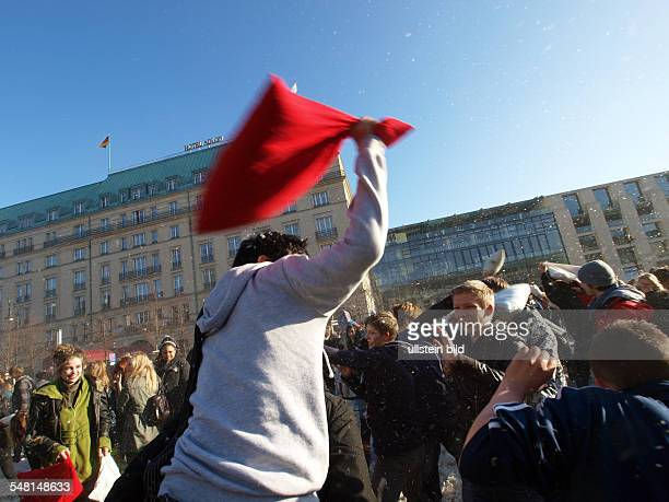 Germany Berlin Mitte Flash mob pillow fight at Brandenburg Gate in the background the Hotel Adlon