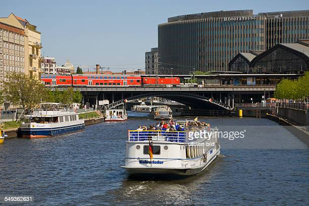 the river 'Spree' with excursion boats railway station 'Friedrichstrasse' with local express train and the office building 'Spreedreieck'