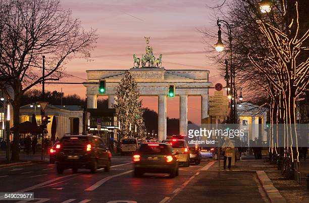 the street 'Unter den Linden' with Brandenburg Gate with christmas illumination and christmas tree in the evening </english>