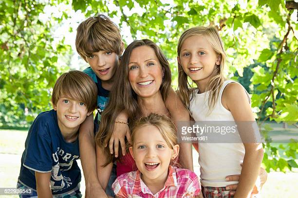 Germany, Berlin, Mother in park with four children