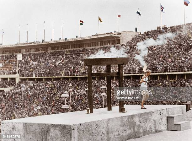 Germany Berlin Olympic Games 1936 The last torch bearer of the Olympics at Berlin longdistance runner Fritz Schilgen standing on the platform above...