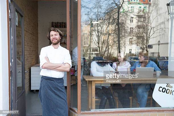 Germany, Berlin, owner and cook of a bistro standing at entrance door