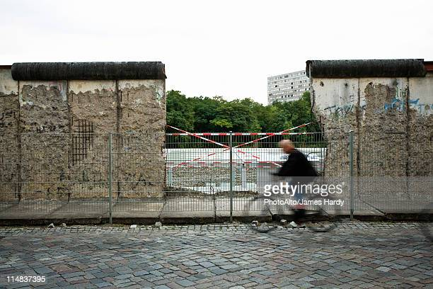 Germany, Berlin, person bicycling past dismantled section of the Berlin Wall