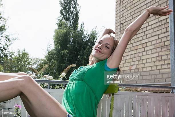 Germany, Berlin, Young woman sitting on chair, stretching