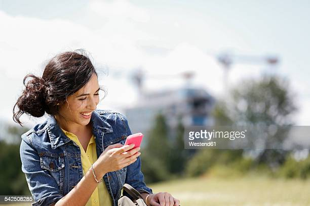 Germany, Berlin, portrait of happy young woman using her smartphone