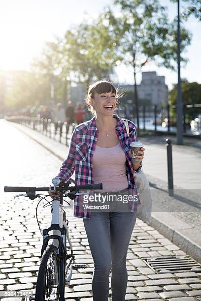 Germany, Berlin, portrait of happy young woman with bicycle and coffee to go