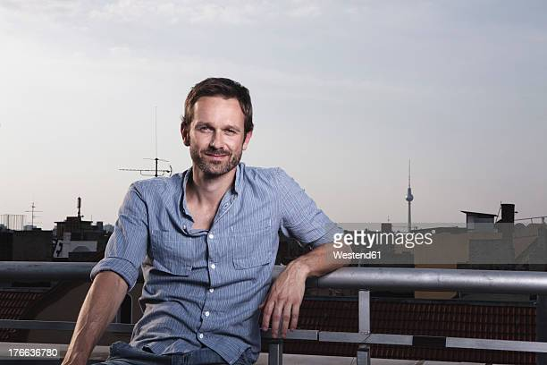 Germany, Berlin, Portrait of man on roof terrace, smiling
