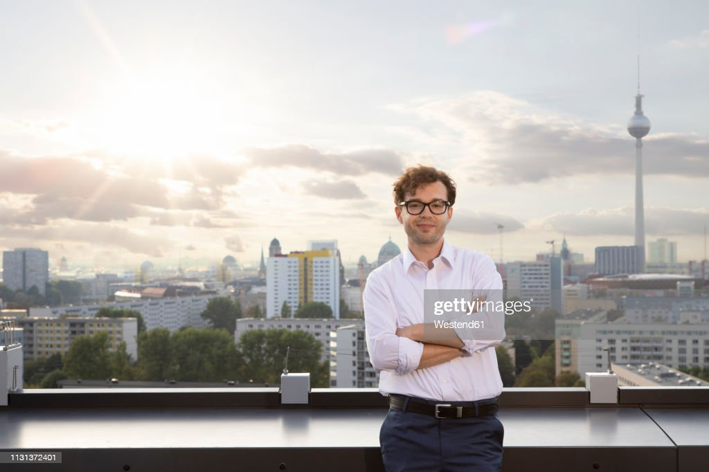 Germany, Berlin, portrait of smiling businessman standing on roof terrace  in the evening : ストックフォト