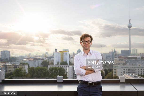 Germany, Berlin, portrait of smiling businessman standing on roof terrace  in the evening