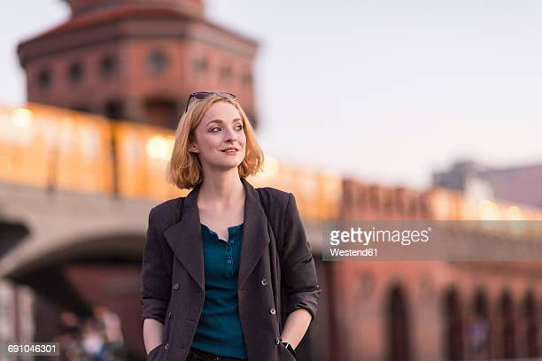 germany, berlin, portrait of smiling young woman in front of oberbaum bridge in the evening - オベルバウムブリュッケ ストックフォトと画像