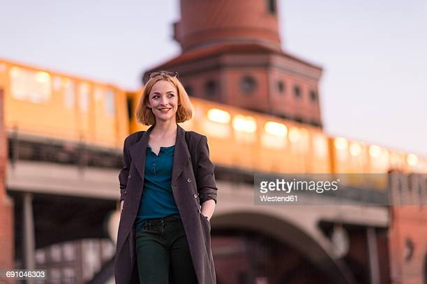 Germany, Berlin, portrait of smiling young woman in front of Oberbaum Bridge in the evening